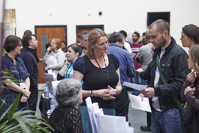 Staff helping students at postgraduate fair