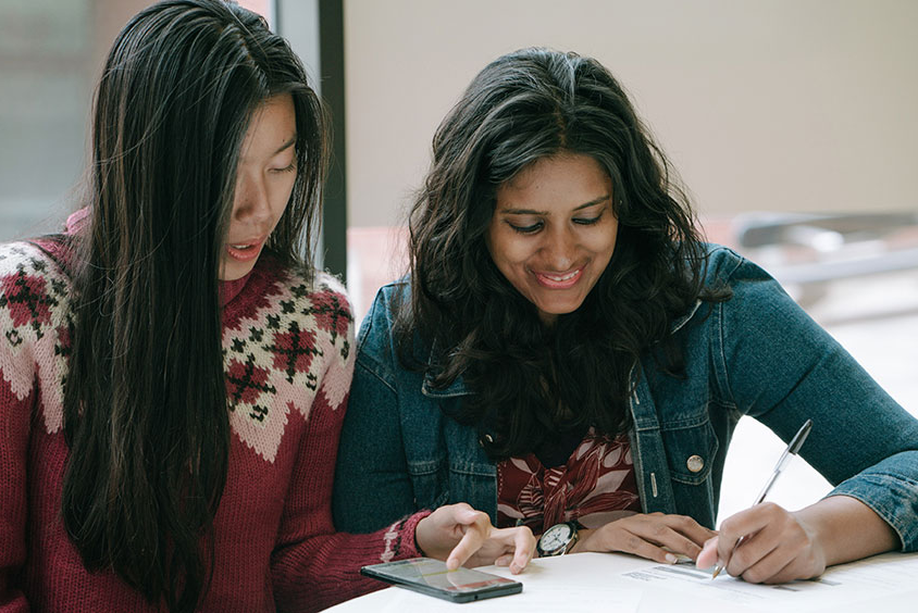 Two international students sat together working at a table
