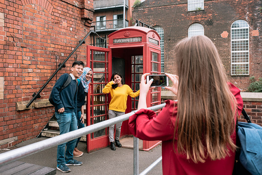 A group of students taking a photo of themselves by a telephone box