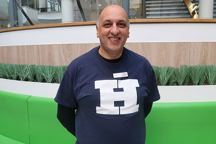 Parent ambassador Zahid stood for a photo at an open day wearing a Team Hallam tshirt.